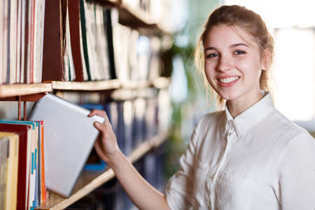 Young pretty girl posing at camera in the library. Education concept.
