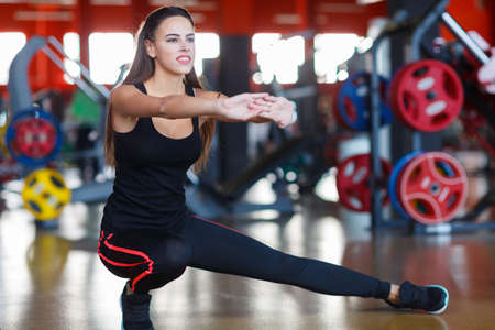 Young athletes girl does exercises at the gym. Sport concept. Stock Photo