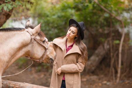 pelo castaño claro: Beautiful young woman in a black hat with a brown horse outdoors. Foto de archivo