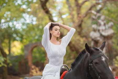 Horseback riding. Beautiful young woman in a white dress riding on a brown horse outdoors.