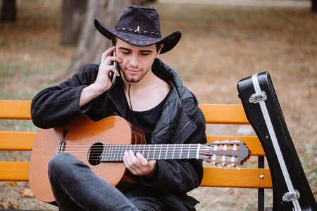 Guitar player speaking phone