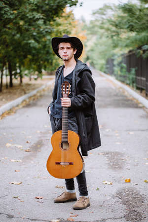 manpower: Autumn portrait of the young guy with guitar