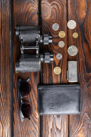 A set of travel accessories on a wooden background. Coins, glasses, binoculars, Passport. Close-up set for travel. Stock Photo