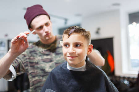 Hairdresser barbershop parihopher strechot small boy sitting on a chair Stock Photo