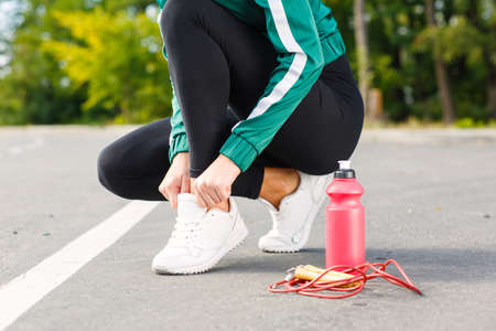 The girl after cardio training on a rope in an autumn park corrects shoelaces on white sneakers.
