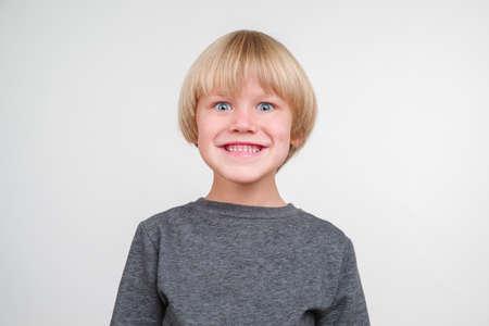 Rapaz pequeno considerável feliz que levanta no estúdio. Foto de archivo - 88463940