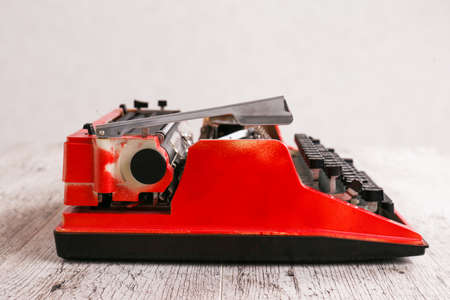 The typewriter is red with paper in it and on a gray wooden table