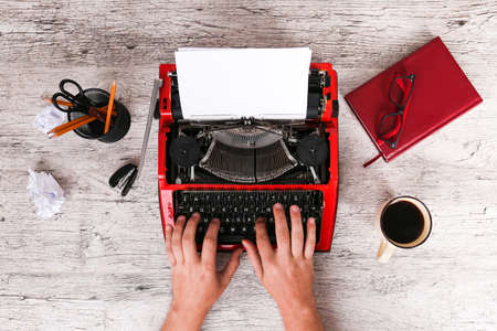 The typewriter is red with paper in it and on a gray wooden table with hands that print