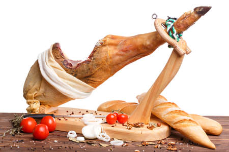 Jamon juicy on a stand close-up on a white isolated background with various vegetables and a glass of wine