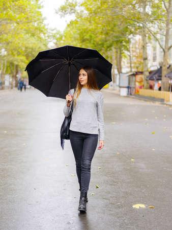 Een meisje met een zwarte paraplu verbergt zich voor de regen Stockfoto