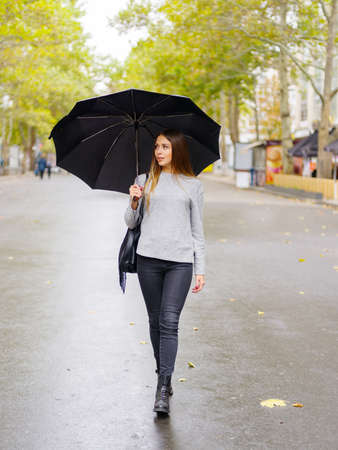 A girl with a black umbrella is hiding from the rain