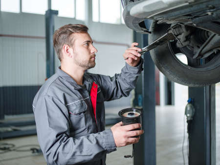 The mechanic makes the wheel from breakage to cars Stock Photo