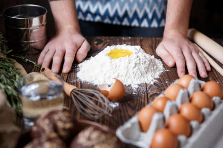 The man put his hands on the kitchen table, which contains ingredients for dough made of flour and eggs. Indoors. Stock Photo