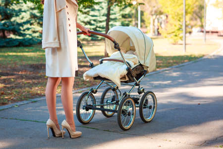 A thin girl in a light coat and high heels is standing near the stroller. Outdoors. Stock Photo