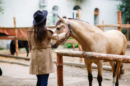 A brunette girl in a coat and hat stroking a horse through a fence. Outdoors. Stock Photo