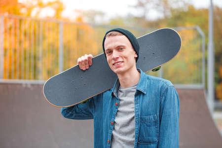 Young skatebarder posing with skateboard in the skatepark. Sport concept. Stock Photo