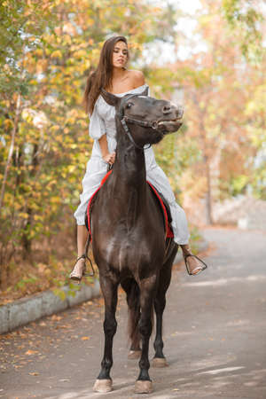 A European girl rides a horse on a road in the fall.