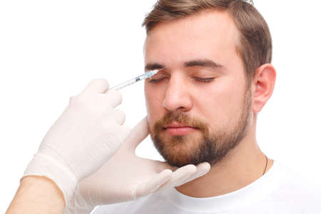 A male botox is injected between the eyebrows. Isolated over white background.