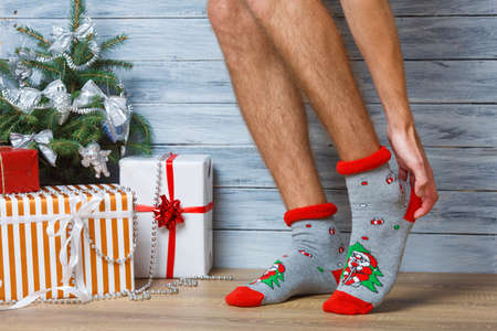 Closeup image of a mans legs in woolen socks on a wooden background. Hairy mens legs in New Years socks. The man straightens his socks with his hands. Stock Photo