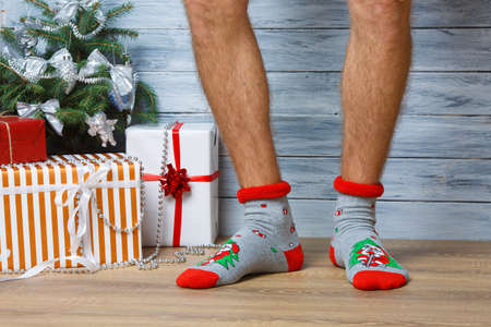 Closeup image of a mans legs in woolen socks on a wooden background. Hairy mens legs in New Years socks. Stock Photo