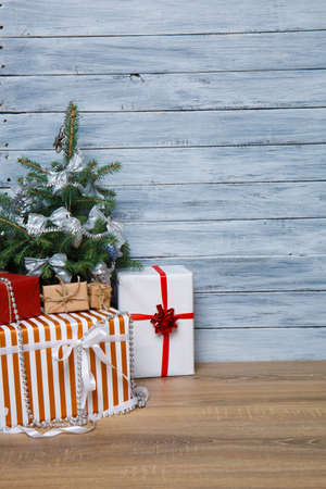 Christmas tree with gifts on a wooden gray background on a light wooden table. Concept of holidays. Stock Photo