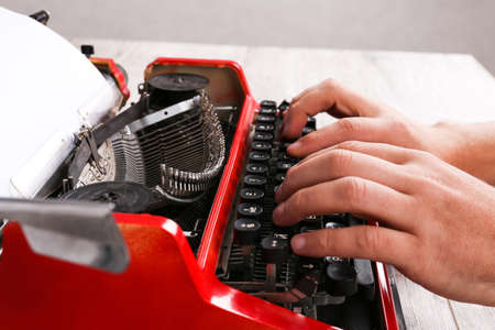 Hands of a man typing on a red typewriter maschine
