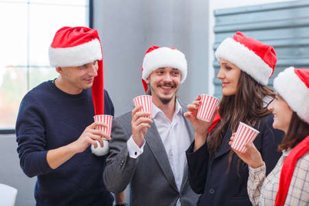 Business young colleagues drink champagne on Christmas Eve