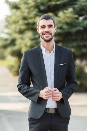 dashing: A young guy with a beard in a suit is standing and smiling on the street.