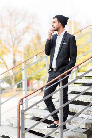 dashing: A young stylish guy with a pensive look is on the steps. Outdoors. Stock Photo