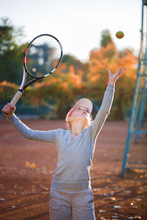 A teenage girl playing tennis on a tennis court