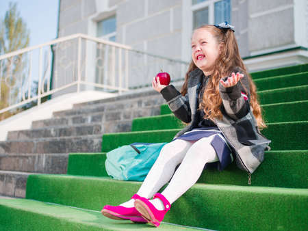 first year student: The girl is sitting on the steps of the school
