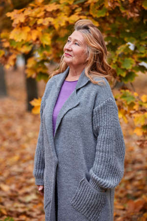 Mature woman in a gray cardigan stands in the park and looks up against a background of yellow leaves. Stock Photo