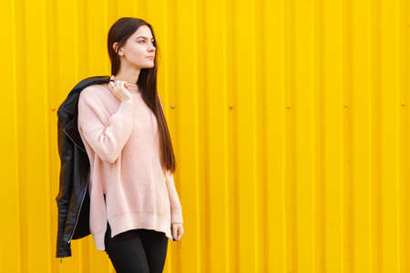 handclasp: A girl posing against a yellow building background Stock Photo