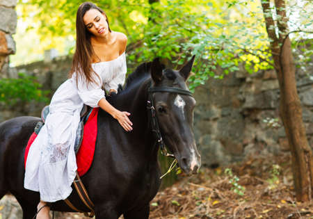 A beautiful brunette on horseback stroking it. In the park. Side view.