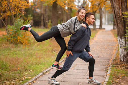 flexing: A young couple doing sports in a park in the fall. The girl climbed onto the guy from behind. Outside. Stock Photo