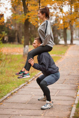 A couple playing sports in an autumn park. The guy crouches holding the girl on his shoulders. Outside. Stock Photo
