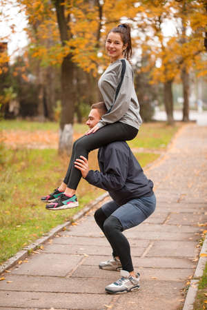 A couple are doing sports in an autumn park. The guy crouches holding the girl on his shoulders. Stock Photo