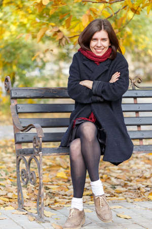 The girl on the bench smiles in the park