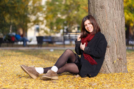 Beautiful girl in black coat and red scarf sitting on the ground near a tree with foliage Stock Photo