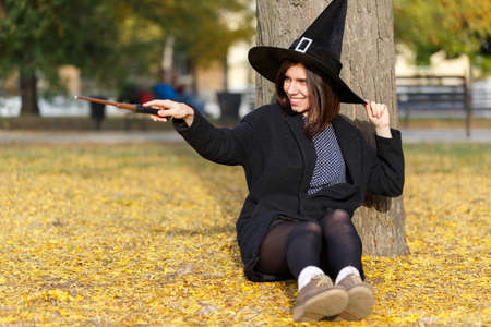 A girl sit at the floor in a magic wizard hat in the park Stock Photo