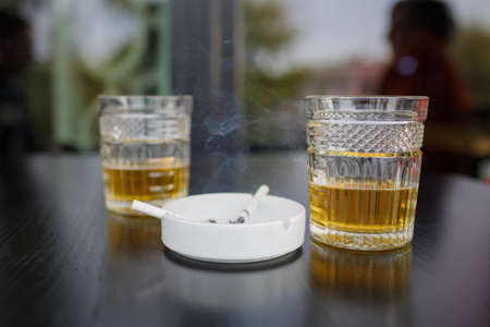 A top view on a two glasses of beer on the dark wooden table. A white ashtray with buutts on the dark background. Close-up of objects. Drink concept.
