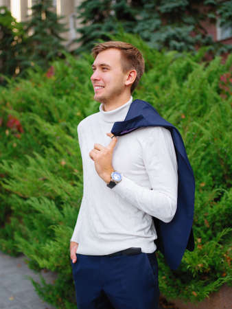 A handsome guy stands on the street, throws his jacket over his shoulder and smiles. Outdoors. Stock Photo