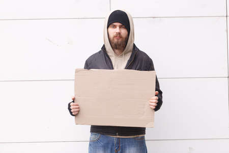 A homeless European appearance stands on the street with an empty cardboard sign. Outdoor.