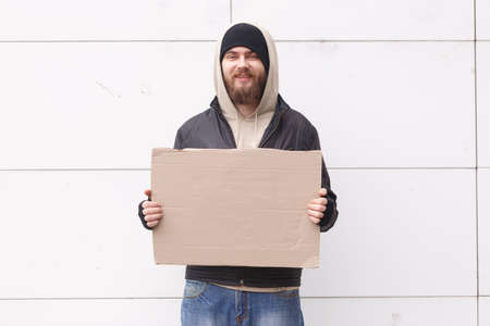 A homeless European-looking man stands on the street near a wall with a cardboard sign and smiles. Outdoor.
