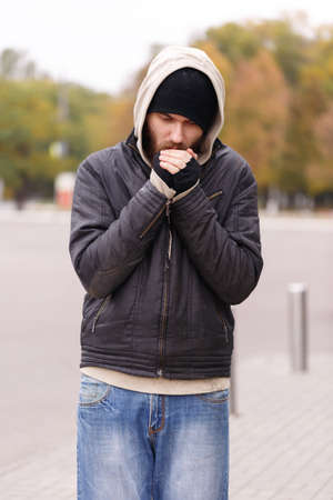 The homeless man in the hood froze walking on the street in cold weather. Outdoor. Stock Photo