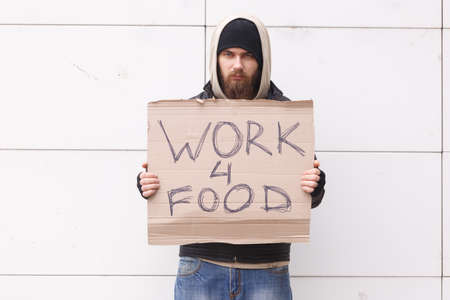 A homeless man with a beard and in a hood stands with a sign. Outdoor.