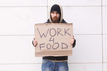 A homeless man with a beard and in a hood stands on the street with a sign about the request for work for food. Outdoor.