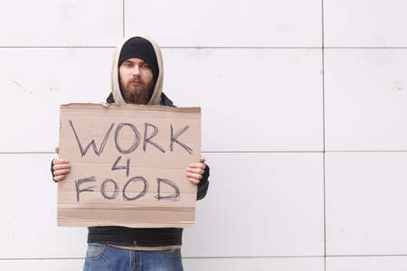 A homeless man stands near a wall in cold weather with a sign about the request for work for food. Outdoor. Stock Photo