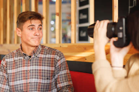 A couple is sitting in a cafe. The girl takes pictures of a guy who grimaces a camera. Inside.