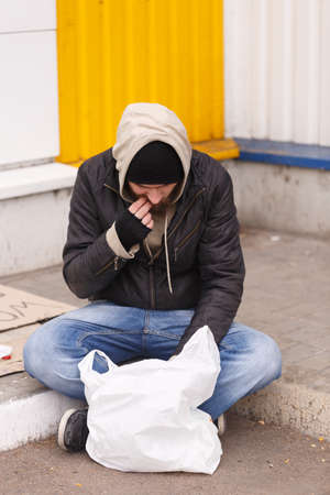 The European homeless man sits on the street on the asphalt and eats from the package. Outdoor. Stock Photo